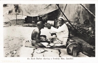 An Arab barber shaving a Swahili man
