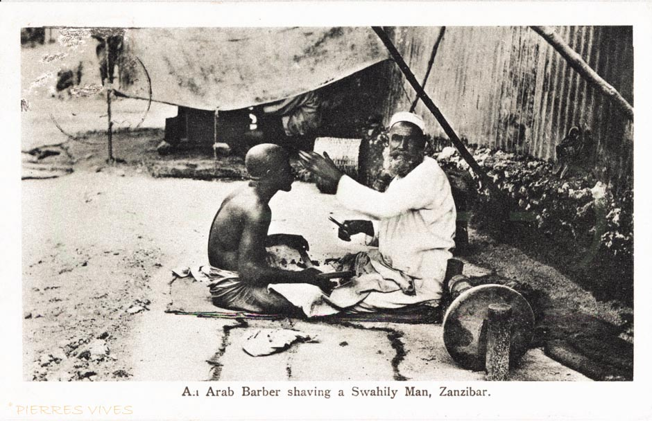 An Arab barber shaving a Swahili man
